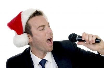 0450-young_man_singing_into_microphone_with_santa_cap.jpg